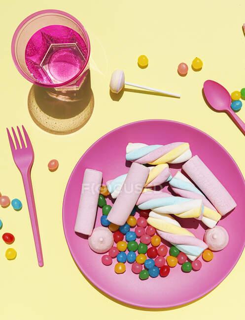 Estudio plano de vaso de agua y plato de plástico lleno de varios dulces - foto de stock