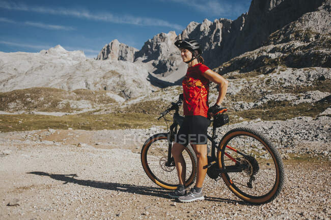 Сприятлива жінка - велосипедист стоїть з гірським велосипедом у Національному парку Пікос - де - Европа (Кантабрія, Іспанія). — стокове фото