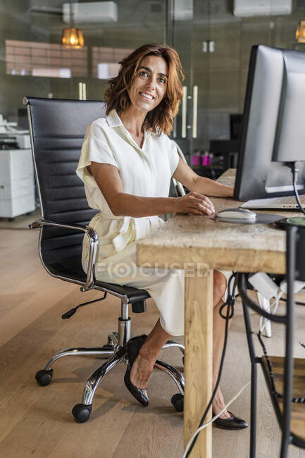 Smiling businesswoman sitting on chair while working in office — Stock Photo