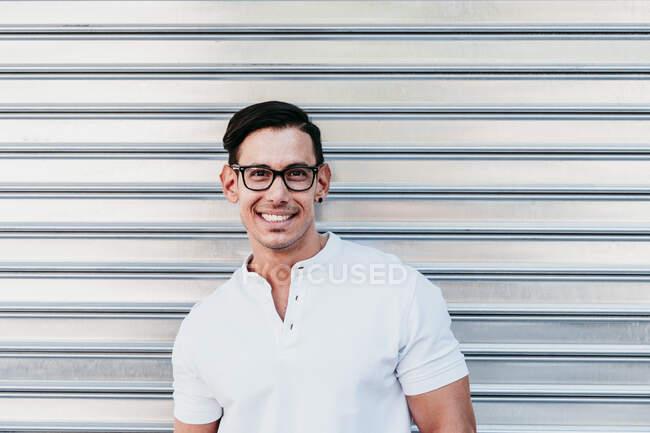 Lächelnder Mann mit Brille gegen Verschluss — Stockfoto