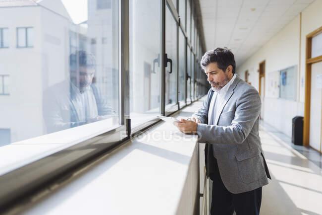 Професор за допомогою цифрової таблетки стоїть біля підвіконня в коридорі в університеті. — стокове фото