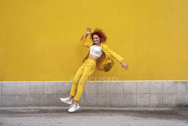 Energetic young woman in yellow suit running and jumping in front of yellow wall — стокове фото