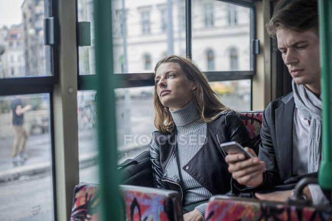 Mulher pensativo sentado com colega do sexo masculino usando telefone inteligente no ônibus — Fotografia de Stock