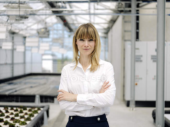 Smiling female owner with arms crossed standing in plant nursery — Stock Photo