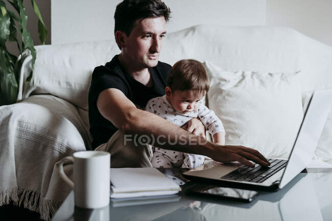 Father using laptop while son sitting on his lap at home — Stock Photo