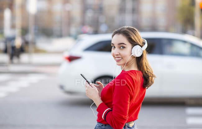 Усміхнена жінка слухає музику через навушники, стоячи на вулиці в місті. — стокове фото