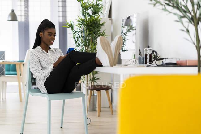 Зайнята жінка пише повідомлення на смарт-телефоні, сидячи вдома. — стокове фото