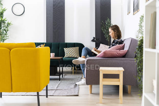 Молодая женщина пишет в книге, сидя дома на диване — стоковое фото