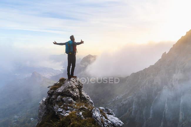 Senderista pensativo con los brazos extendidos de pie en el pico de la montaña durante la salida del sol en los Alpes bergamascos, Italia - foto de stock