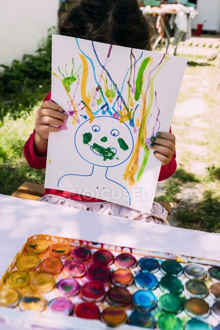 Menina mostrando pintura enquanto sentado à mesa no quintal — Fotografia de Stock
