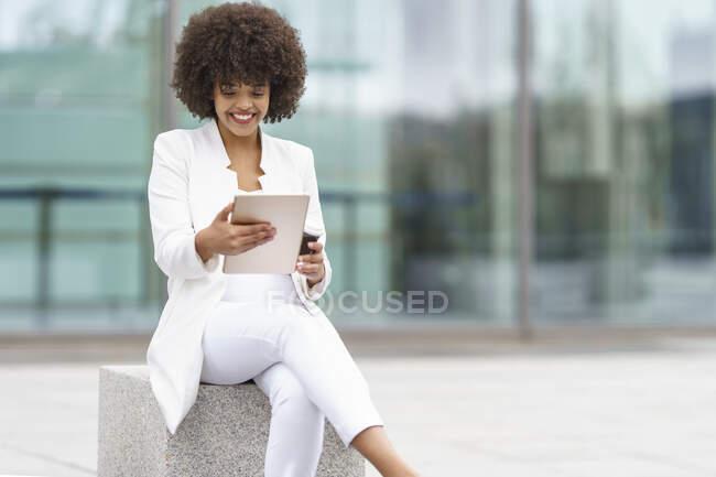 Imprenditrice sorridente mentre utilizza tablet digitale contro la costruzione — Foto stock
