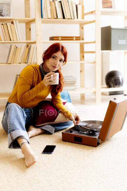 Junge Frau trinkt Kaffee, während sie zu Hause am Plattenteller sitzt — Stockfoto