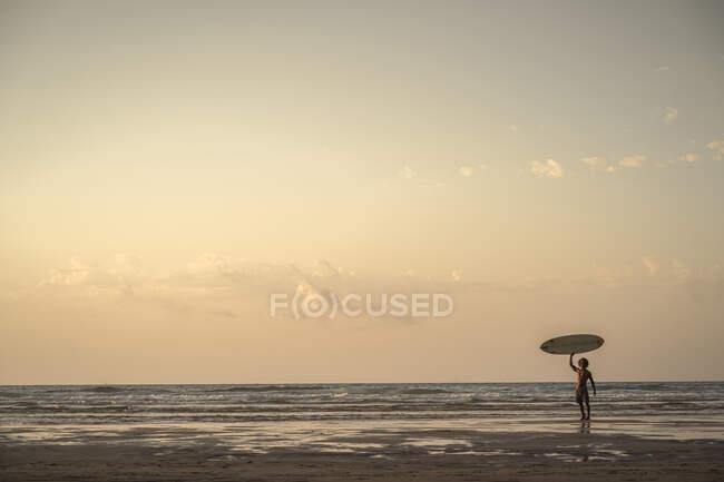 Giovane con tavola da surf in spiaggia contro il cielo durante il tramonto — Foto stock