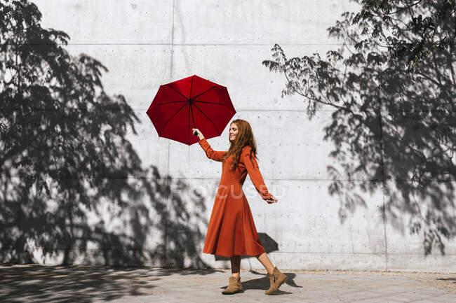Женщина в красном платье держит красный зонтик, стоя напротив стены тени дерева — стоковое фото