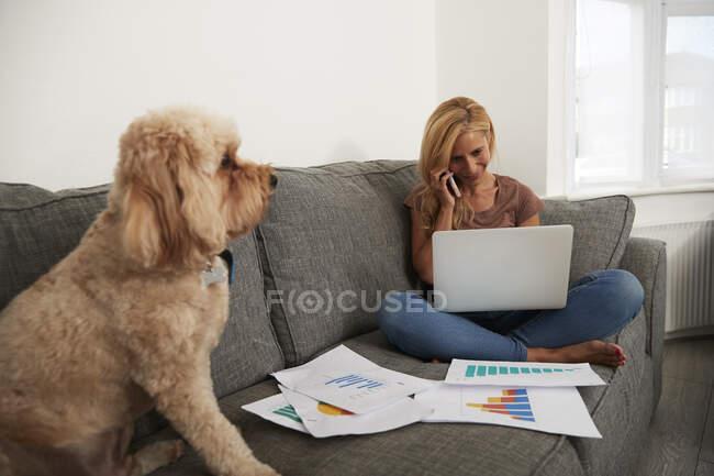 Доросла жінка розмовляє на смартфоні, а ноутбук сидить удома. — стокове фото