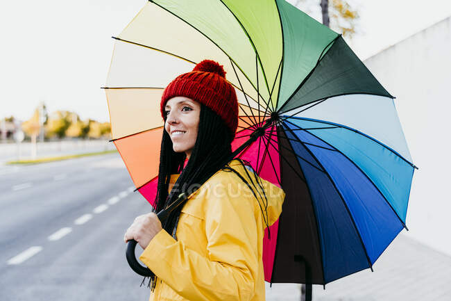 Woman holding colorful umbrella looking away while standing on street — Stock Photo