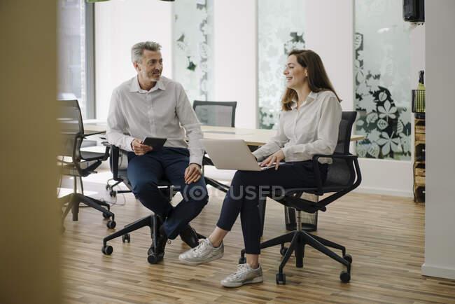 Безробітна жінка використовує ноутбук, сидячи біля бізнесмена в офісі. — стокове фото