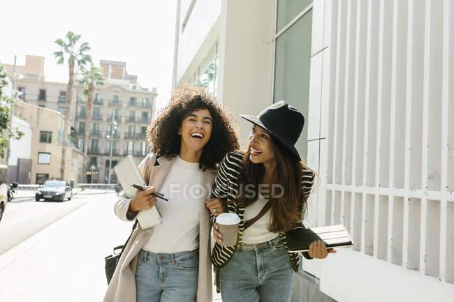 Femmes d'affaires riant tout en marchant dans la rue pendant la journée ensoleillée — Photo de stock