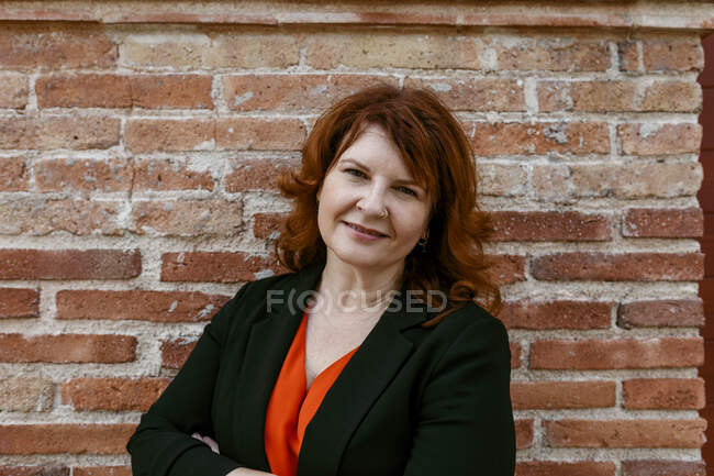 Smiling woman standing against brick wall — Stock Photo