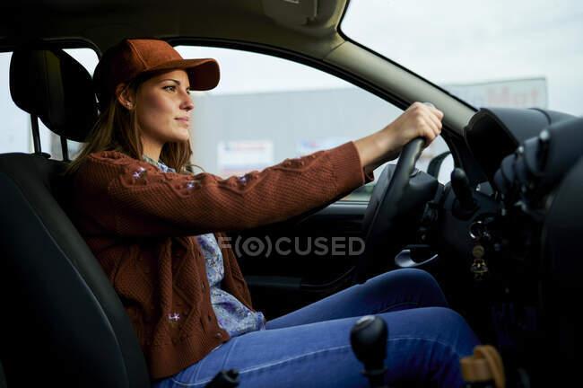 Молода жінка водить машину в місті. — стокове фото