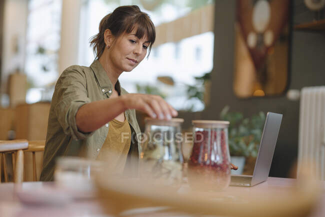 Зайнята жінка закриває скляні посудини, стоячи в кафе. — стокове фото