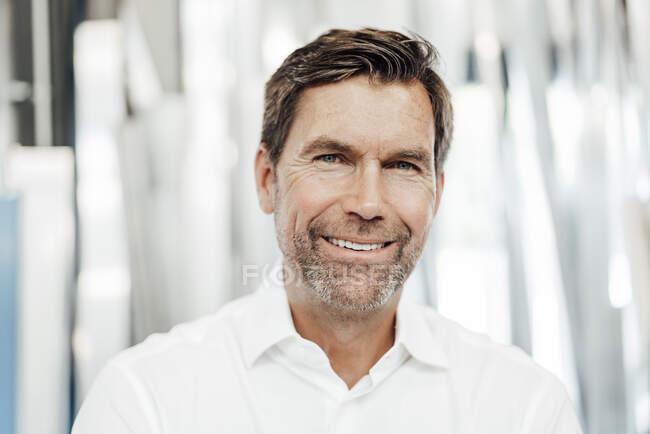 Sonriente hombre de negocios maduro y seguro en la industria - foto de stock