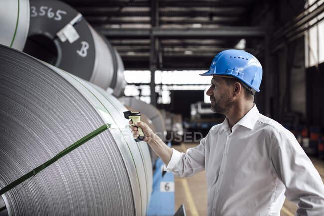 Hombre escaneando código de barras en rollos de acero mientras está de pie en la industria - foto de stock