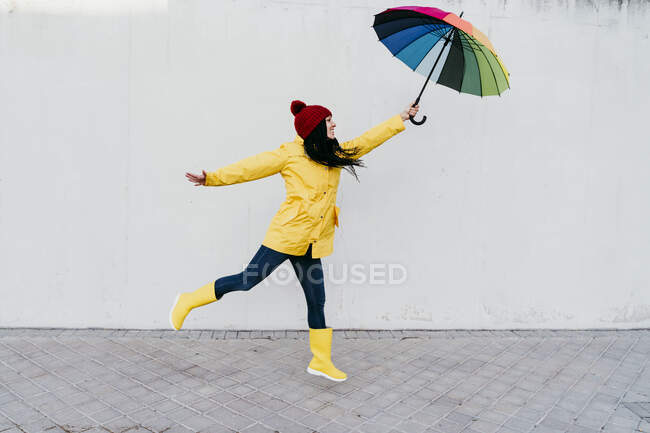 Woman with arms outstretched holding colorful umbrella while standing on footpath against wall — Stock Photo