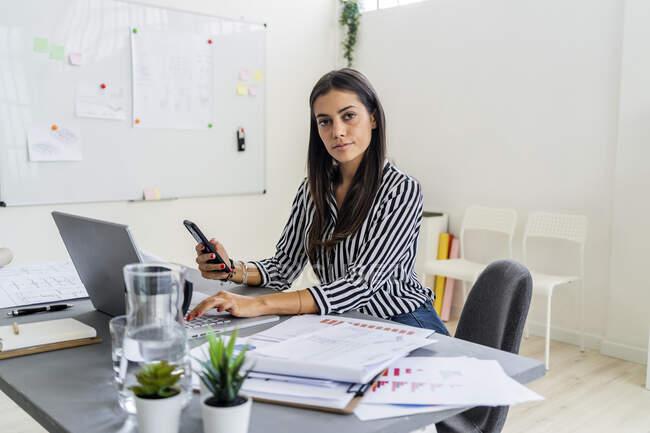 Selbstbewusste Designerin sitzt mit drahtlosen Technologien am Schreibtisch im Büro — Stockfoto