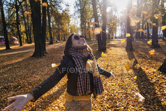 Smiling beautiful woman with arms outstretched enjoying while standing under falling dry leaves at park during autumn — Stock Photo