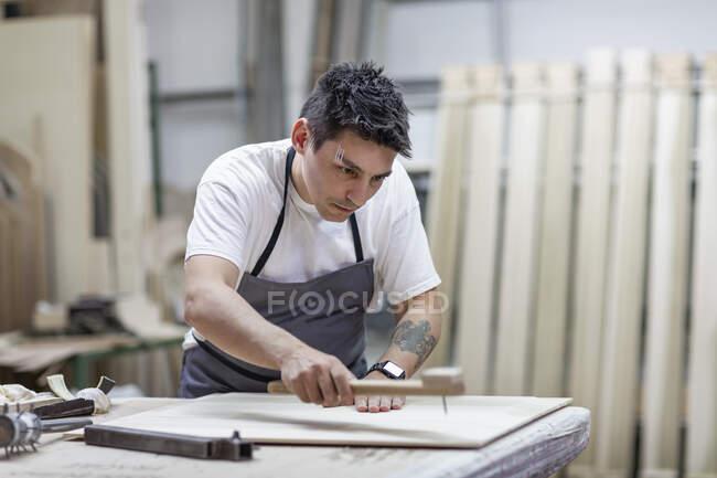 Künstler gestaltet Holz durch traditionelle Methode im Stehen in der Werkstatt — Stockfoto