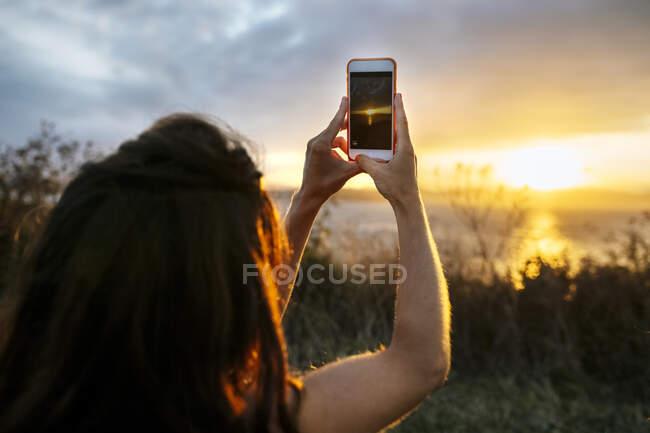Mujer joven fotografiando el cielo del atardecer a través del teléfono inteligente - foto de stock