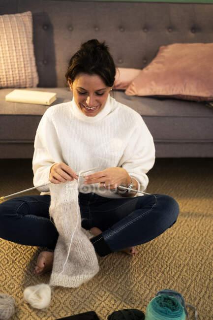 Посмішка серед дорослої жінки, яка плете вовну вдома. — стокове фото