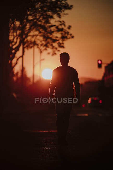 In silhouette of man walking on road during sunset in city - foto de stock