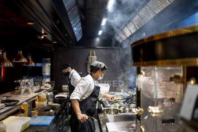 Chefs wearing protective face mask preparing dish in restaurant kitchen — Stock Photo
