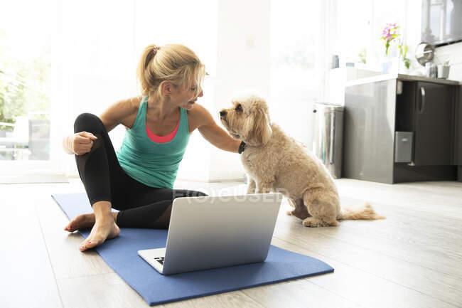 Зріла жінка, яка сиділа на маті з допомогою ноутбука вдома. — стокове фото