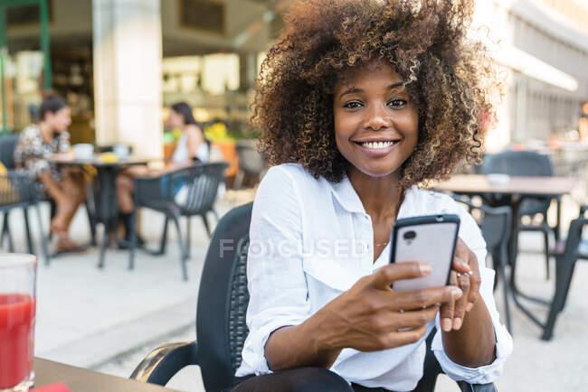 Сообщения женщины на смартфоне, сидя в кафе — стоковое фото