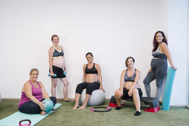 Улыбающаяся группа беременной женщины, занимающаяся спортом в студии йоги — стоковое фото