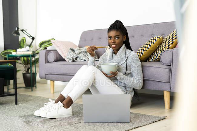 Усміхнена жінка їсть локшину, сидячи на підлозі у вітальні. — стокове фото