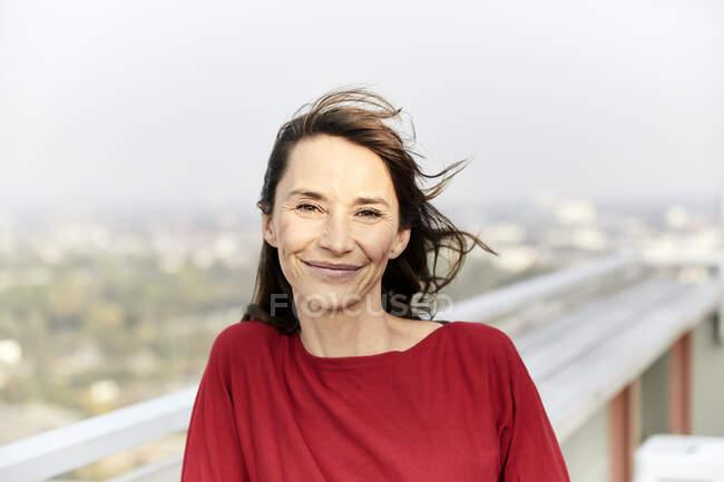 Mujer sonriente con el pelo soplando de pie en la terraza del edificio - foto de stock