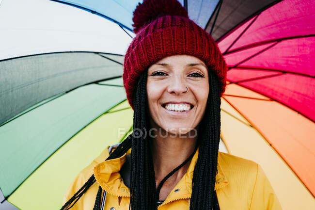 Зблизька усміхнена жінка тримає парасольку. — стокове фото