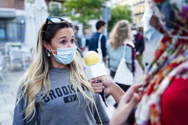 Mujer adulta respondiendo a periodista en la ciudad durante COVID-19 — Stock Photo