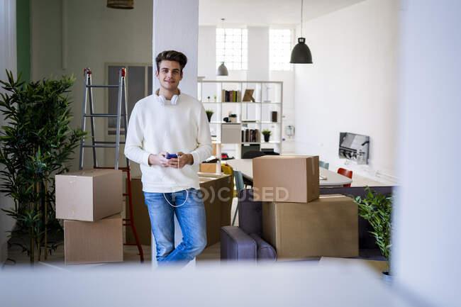 Улыбающийся молодой человек в наушниках держит мобильный телефон напротив колонны в новом доме — стоковое фото