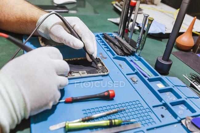 Técnico examinando telefone celular danificado na bancada de trabalho da oficina — Fotografia de Stock