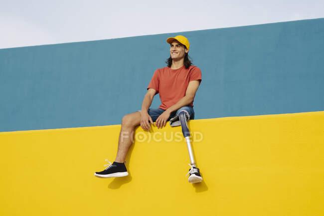 Усміхаючись, молодий чоловік сидить навпроти багатокольорової стіни. — стокове фото