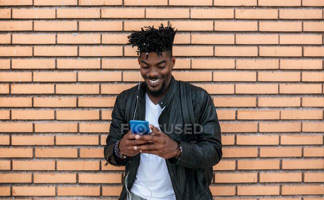 Sonriente hombre adulto medio usando chaqueta de cuero usando teléfono móvil mientras está de pie contra la pared de ladrillo - foto de stock