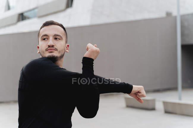 Jovem desportista esticando as mãos enquanto está ao ar livre — Fotografia de Stock