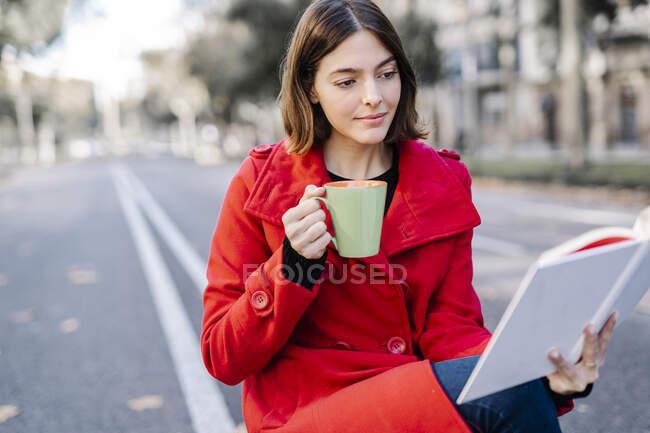 Giovane donna che indossa giacca invernale prendendo il caffè durante la lettura del libro in strada — Foto stock