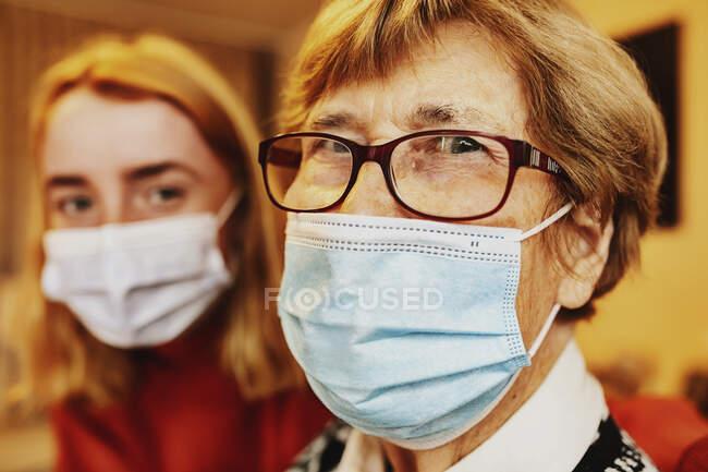 Abuela con mascarilla y anteojos mirando mientras está sentada junto a su nieta en casa - foto de stock