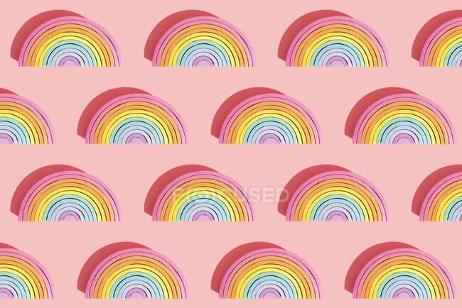 Image multiple de jouets arc-en-ciel en bois coloré sur fond rose — Photo de stock